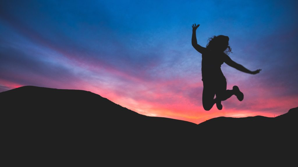 dark-silhouette-jumping-with-sun-setting-over-mountians-in-the-background