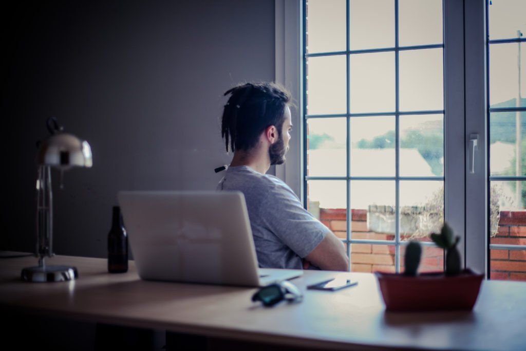 man-sitting-at-desk-facing-towards-window-with-arms-crossed