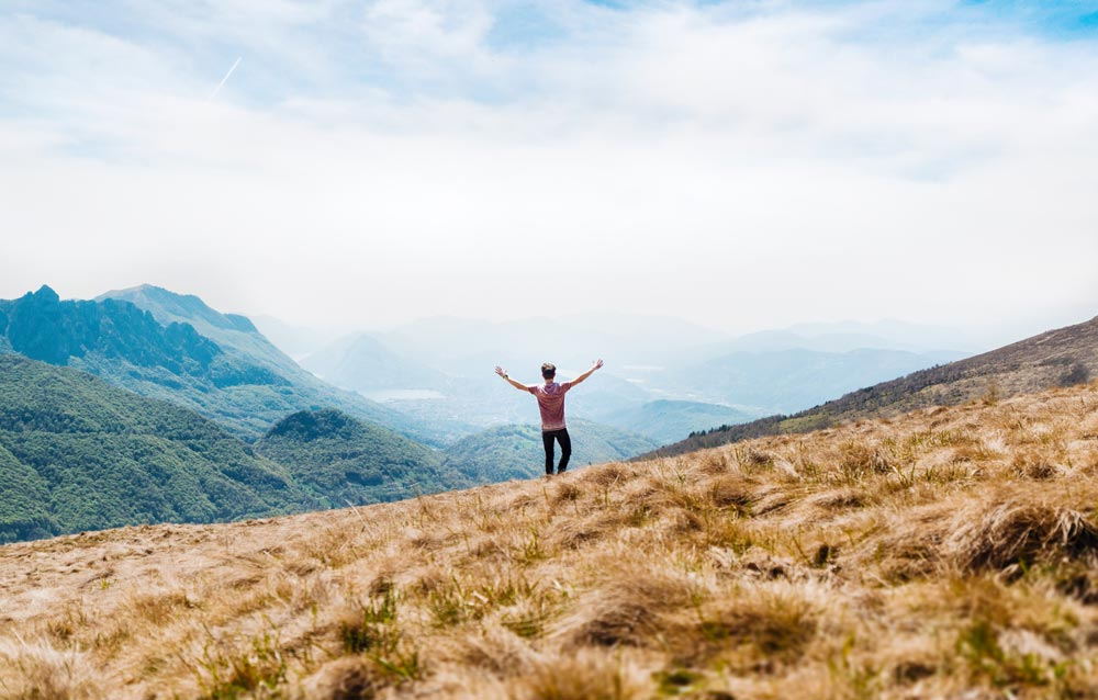 man-standing-on-top-of-mountians-looking-at-the-view-with-arms-thrusted-upwards