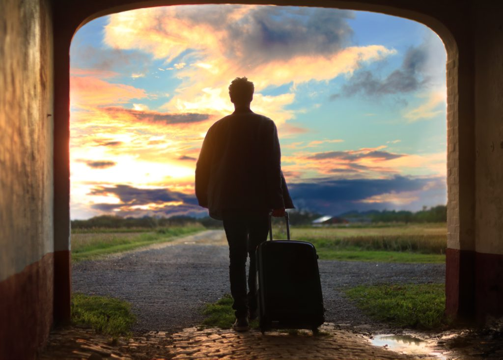 man-walking-into-sunset-with-rolling-suitcase
