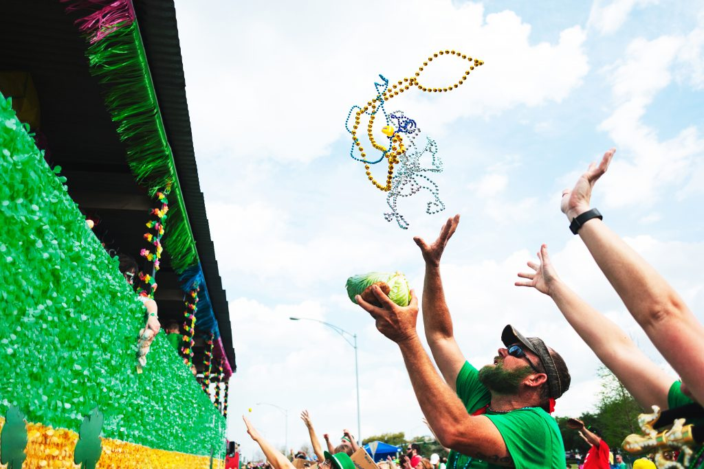 Man catching beads from float