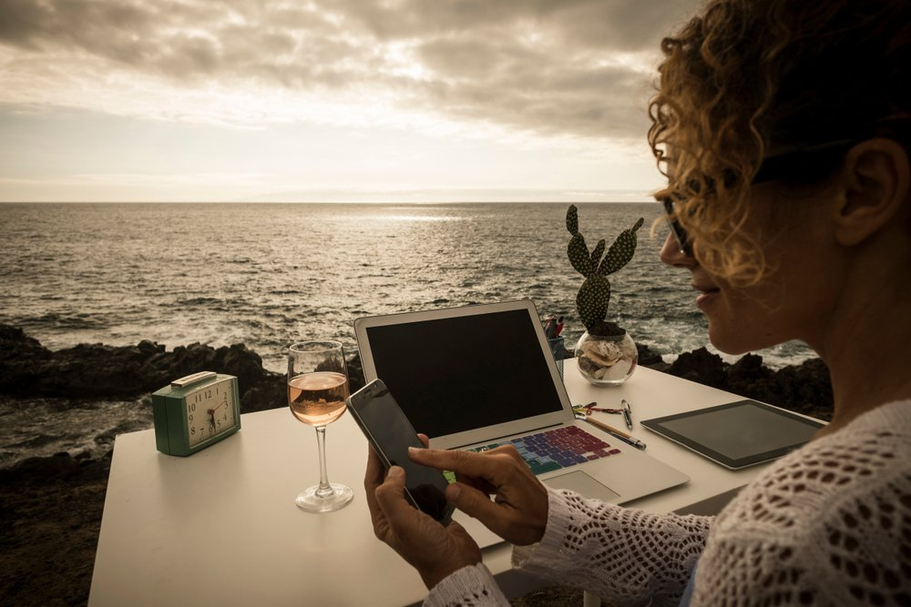 Digital nomad woman working remotely from her international apartment with an ocean view. This is a common work setup for nomadic entrepreneurs.